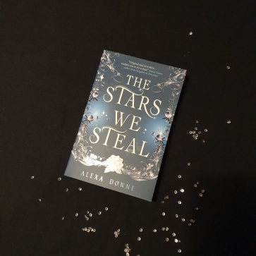A Black and Blue book cover with silver sparkles. Placed on a black table cloth with gemstones around it.