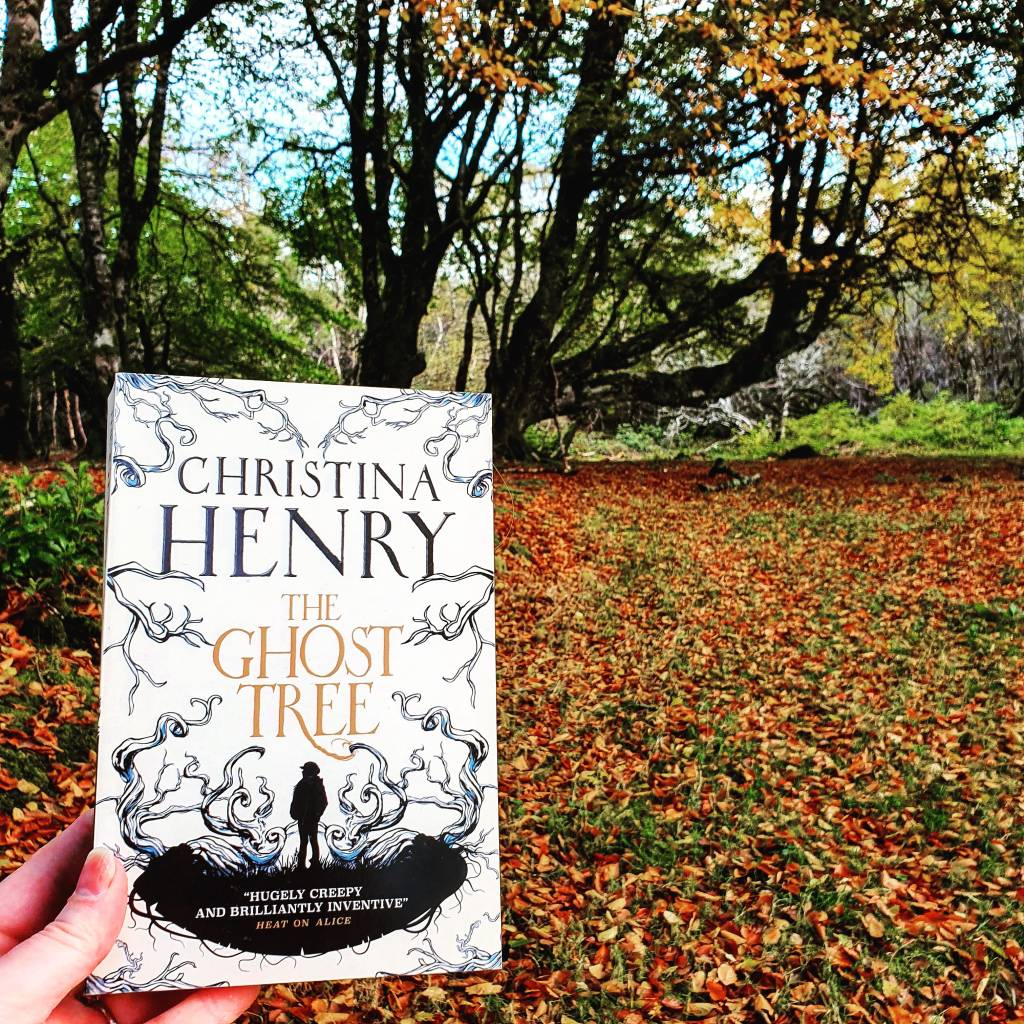 The Ghost Tree by Christina Henry (White cover with silhouettes) is held up against an autumnal forest scene.