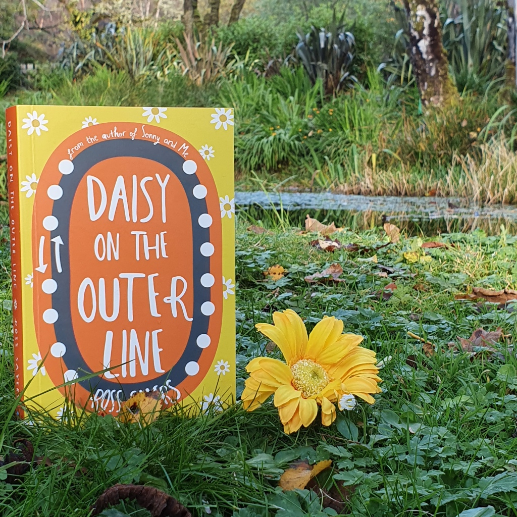 Daisy on the Outer Line Cover is featured in a garden next to a small loch